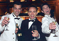 three costumed male singers toasting