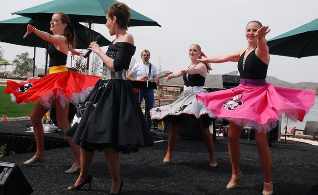 four female performers dressed in fifties style poodle skirts guitarist in background