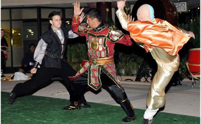 three costumed martial arts performers in battle