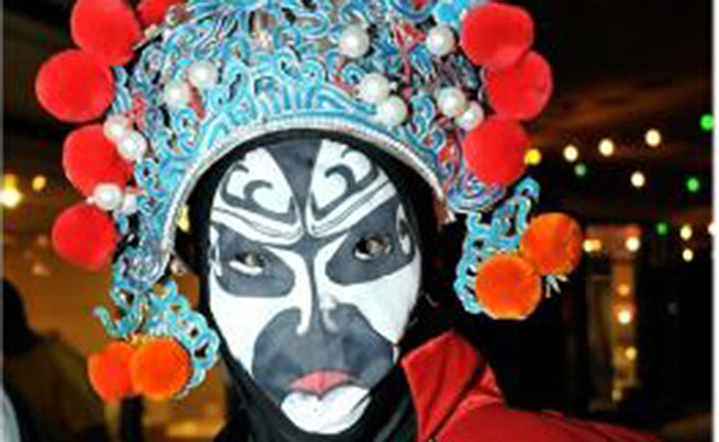 asian performer with painted face and headpiece