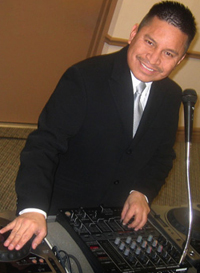 hispanic DJ in black suit behind console