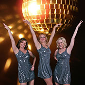 three costumed disco dancers in front of mirror ball