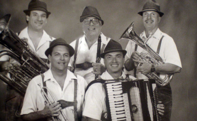 five lederhosen attired polka musicians with instruments