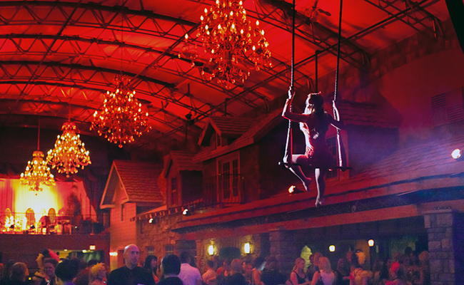 Female aerialist swinging above a crowd