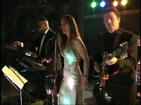 female in shiny white dress with two musicians playing keys and guitar