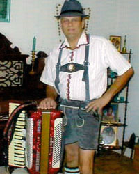 male Accordianist dressed in lederhosen with red accordion