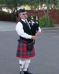 male Bagpiper attired in kilts and cap