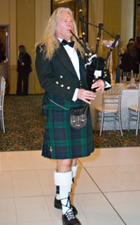 male Bagpiper with long blonde hair and kilts