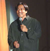 Asian male comedic in black holding microphone