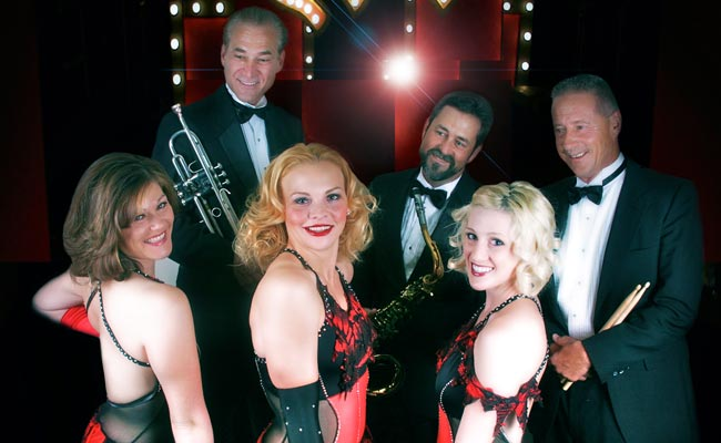 three female cabaret dancers posing with three male musicians