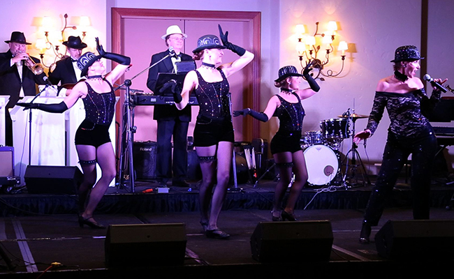 three cabaret dancers and singer in costume with band