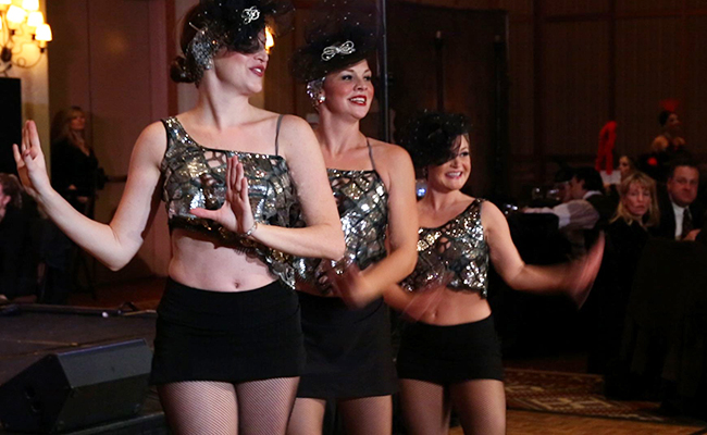 three costumed cabaret tap dancers with audience looking on