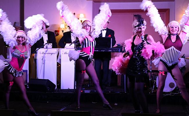 three burlesque cabaret dancers with boas and female vocalist