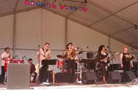 three female singers three male musicians on stage