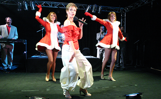 female singer and three dancers on stage dressed in holiday red and white