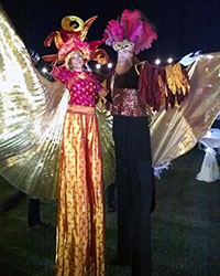 female and male costumed stiltwalkers with ribbons