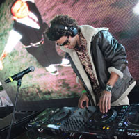 afro american DJ leaning over console with bomber jacket, sun glasses