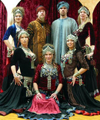five female performers two male musicians in Mid-Eastern attire