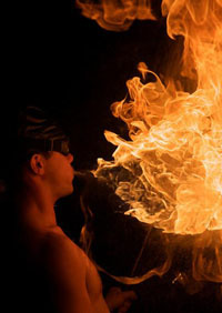 male Fire eater blowing fire