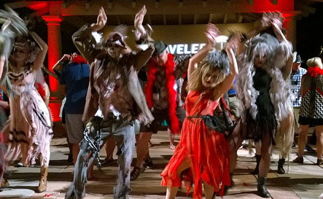four costumed thriller flash mob dancers with guests dancing in background