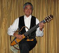 male guitarist in tuxedo vest