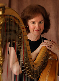 female harpist posing with harp