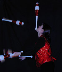 female juggler juggling bowling pins
