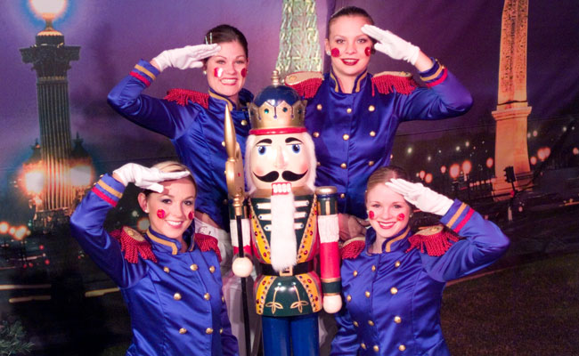 four saluting white gloved toy soldier costumed performers with tall nutcracker