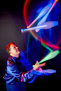 male juggler throwing lit clubs