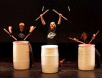 three drummers playing trash cans