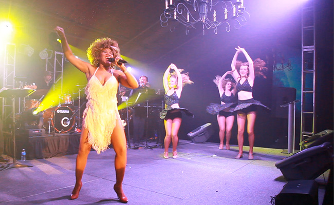 Tina Turner impersonator singing with drums in background