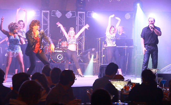 troupe of Tina and Bruce and Mick impersonators with dancers and band