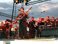 male latin singer guitarist with band in background