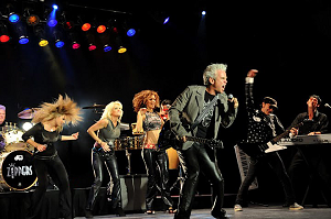 four male musicians and three female singers performing on stage