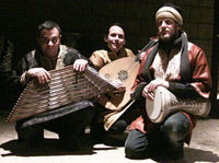 three male musicians kneeing holding moroccan instruments