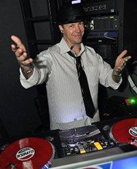 male dj behind console, with hands up and hat on