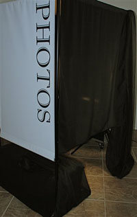 black draped photo booth with a photos banner