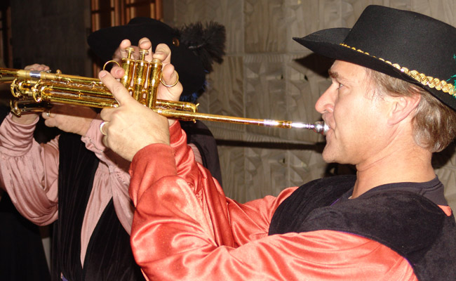 costumed renaissance trumpeter playing a musical fanfare