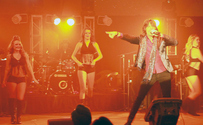 Mick Jagger impersonater singing with female dancers and band