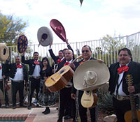 ten mariachi musicians waving somberos in air