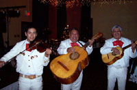 three male mariachi musicians in white outfits