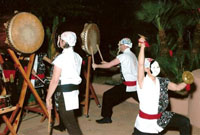 three masked japanese drummers with drums