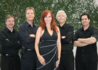 four male musicians in black with female singer