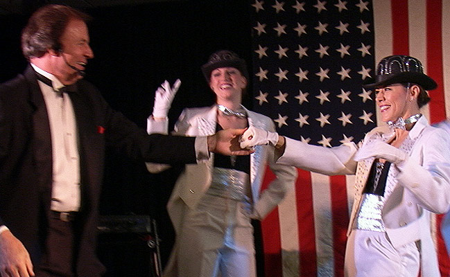 uso band leader dancing with female performer in white tuxedo