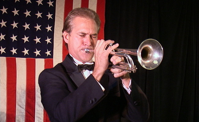 trumpet musician playing with american flag as backdrop