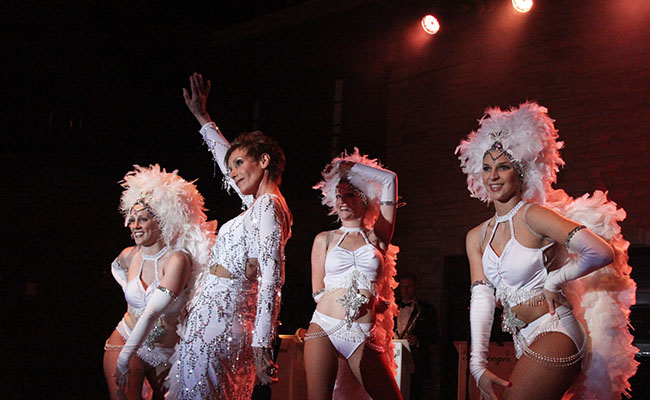 costumed singer with three show girls in white