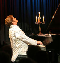 male pianist playing baby grand piano with candleabra